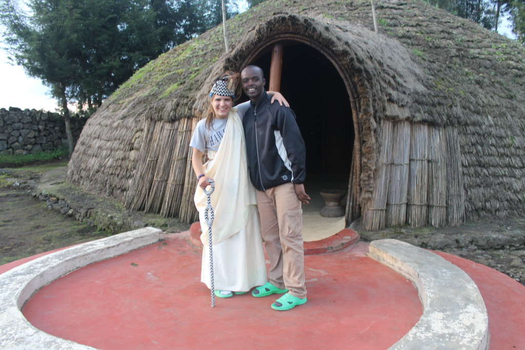 "In traditional clothing in front of King's Hut with her friend Cederick who ""taught me everything"". His grandparents & parents were poachers, but he is a conservationist!"